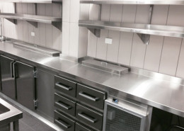 A stainless steel bench and shelving installed in a commercial kitchen