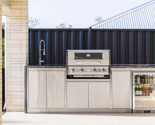 A bespoke stainless steel outdoor barbecue area complete with cabinetry, sink and wine fridge