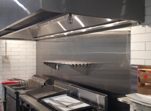 Stainless steel splashback installed in a commercial kitchen