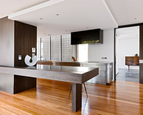 A modern kitchen featuring wooden floorboards and stainless steel cabinetry
