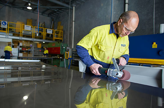 A Metro Steel Services team member using a buffing tool