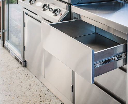 Close up of custom stainless steel cabinetry and open drawer