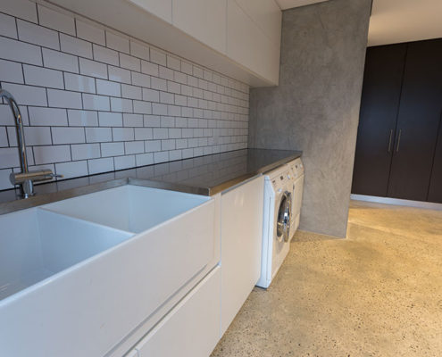 A bespoke laundry featuring a stainless steel bench top
